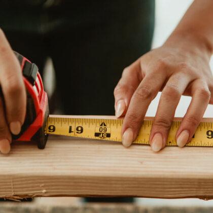 Female carpenter measuring the lumber - Image by © rawpixel